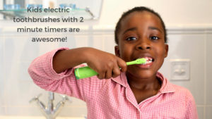 A child using an electric toothbrush with a 2 minute timer