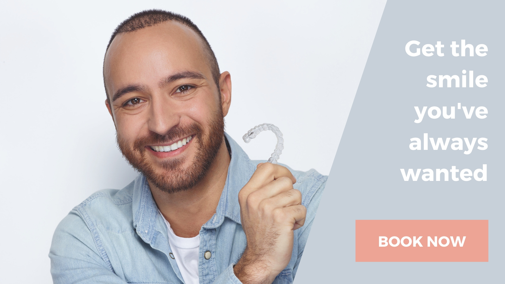 Invisalign aligner being held by a smiling man who is having his crooked teeth aligned